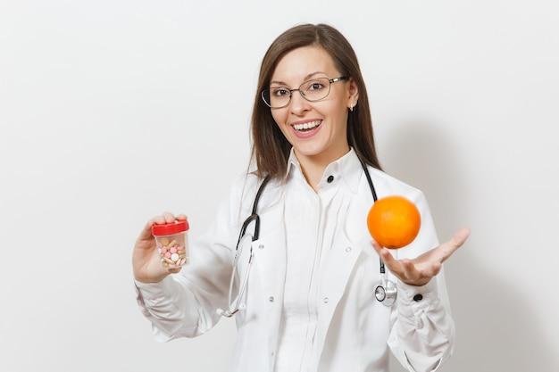 청진 기, 흰색 배경에 고립 된 안경 웃는 자신감이 젊은 의사 여자. 의료 가운을 입은 여성 의사는 오렌지색 약이 든 병을 들고 있습니다. 의료 인력, 의학 개념입니다.