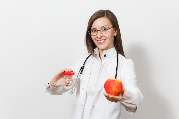 Усмехаясь уверенно молодая женщина доктора со стетоскопом, стеклами изолированными на белой предпосылке. женщина-врач в медицинском халате держит бутылку с таблетками, красное яблоко. медицинский персонал, концепция медицины.