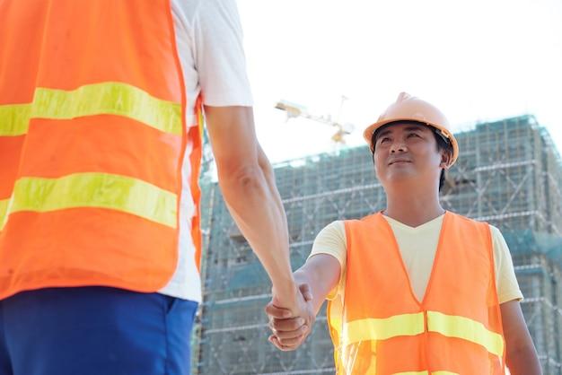 初めて現場に来たときに請負業者の手を振る笑顔のくびれ作業員