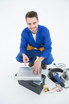 Smiling construciton worker pointing at laptop