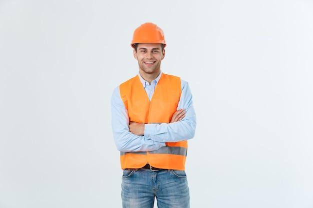 腕を組んでポーズをとる笑顔の建設エンジニア。灰色の背景の上に分離。