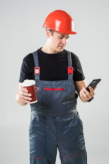 Smiling construction worker in helmet drinking coffee to go use phone