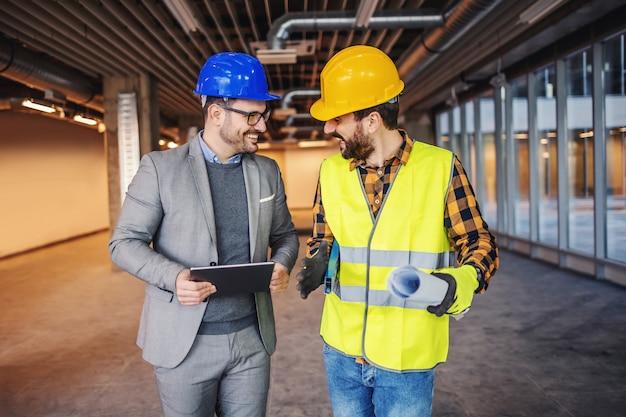 Улыбающийся рабочий-строитель в рабочей одежде держит чертежи и разговаривает с главным архитектором о реализации нового проекта.