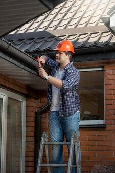 家の屋根の下のステップはしごで建設労働者の笑顔
