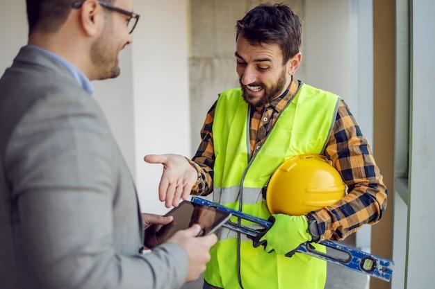 태블릿에 대한 설명서를 가리키고 그의 감독자와 이야기하는 건설 노동자 미소.