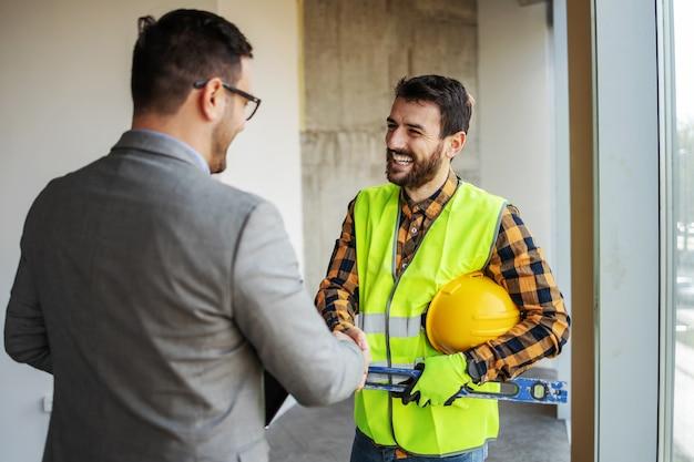 建設過程で建物に立っている間、監督者と握手する笑顔の建設労働者