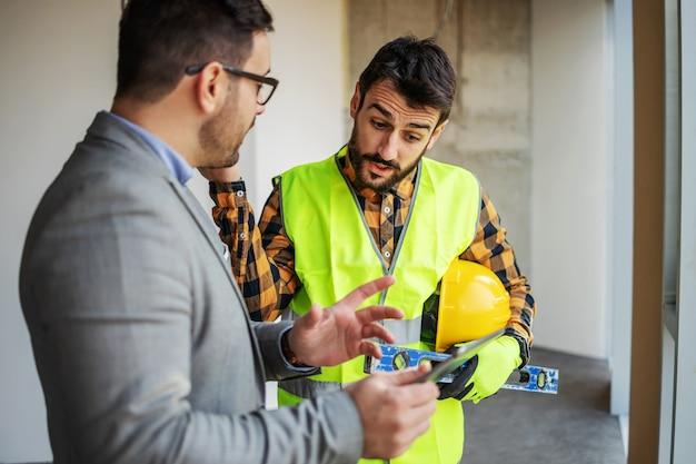 감독자와 함께 서서 건설 과정에서 건물에 서있는 동안 태블릿에 청사진을보고 웃는 건설 노동자.