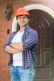 Улыбающийся рабочий-строитель со сложенными руками позирует против двери нового дома