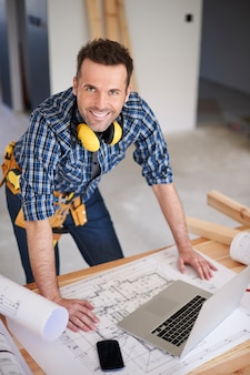 Smiling construction worker with plans and a laptop