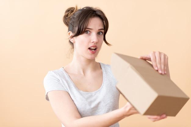 目を大きく開いて笑顔の消費者の女の子は、オンラインストアから箱を開きます。