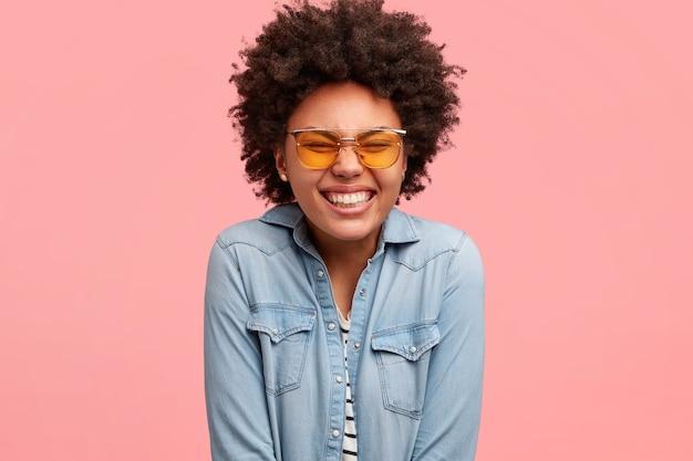 La ragazza sorridente e soddisfatta dalla pelle scura chiude gli occhi e sorride ampiamente, essendo di buon umore, ride a una battuta divertente, indossa una camicia di jeans, modella sul muro rosa. buone emozioni e sentimenti concetto