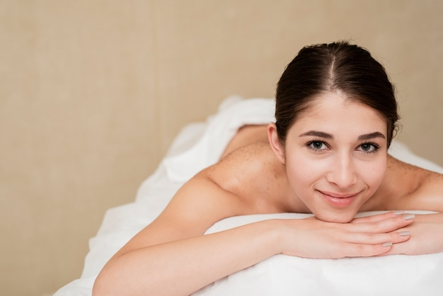 Smiling content woman on massage table at spa
