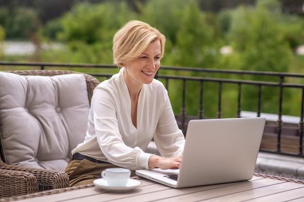 Улыбающаяся довольная кавказская белокурая женщина-надомник сидит за деревянным столом и печатает на своем ноутбуке