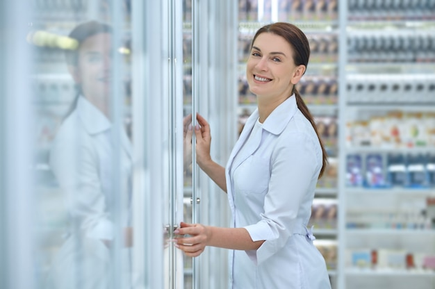 Smiling contented caucasian female pharmacist in a clean white robe touching the pharmacy display cabinet