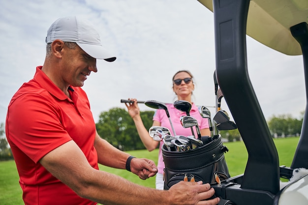 Smiling contented golf tutor in a cap looking at the golf bag full of clubs