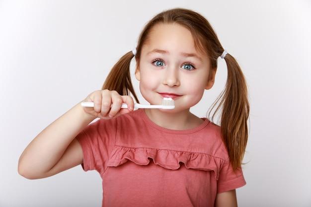 歯を磨きながら満足している小さな女の子の笑顔
