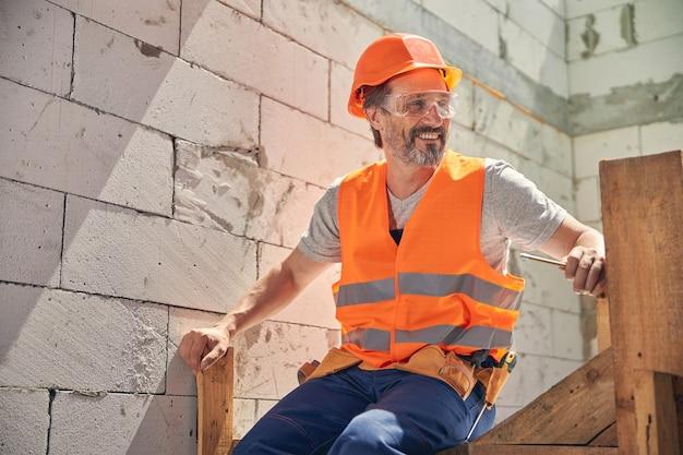 Улыбающийся довольный рабочий мужчина в жилете безопасности и шлеме сидит на лестнице