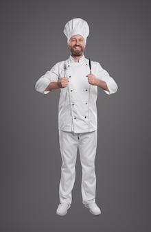 Улыбающийся повар в униформе шеф-повара с вилкой и ножом