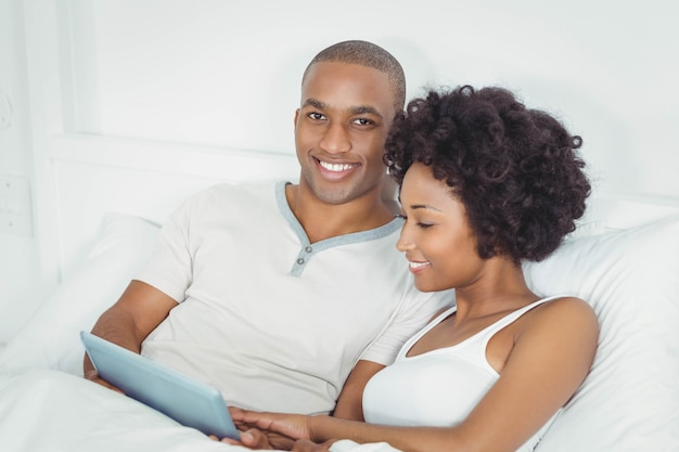 Smiling couple at bed using tablet together