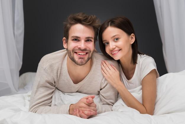 Coppia sorridente a letto