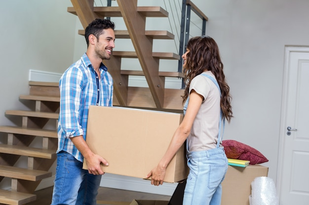 Smiling couple carrying cardboard box