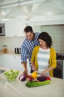 台所で野菜を刻んで笑顔のカップル
