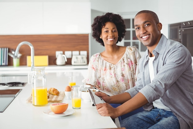 Smiling couple eating breakfast together in the kitchen at home