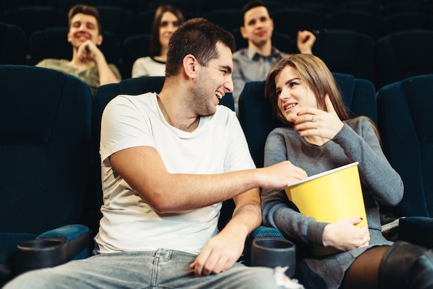 Smiling couple eats popcorn while watching movie in cinema. showtime, comedy film