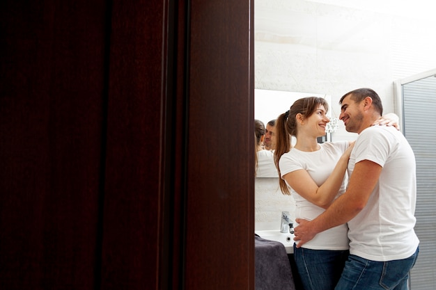 Smiling couple embracing in bathroom