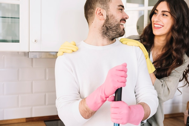 Smiling couple embracing and cleaning