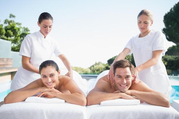 Улыбающаяся пара, наслаждаясь парами массаж у бассейна