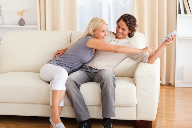 Smiling couple fighting for the remote