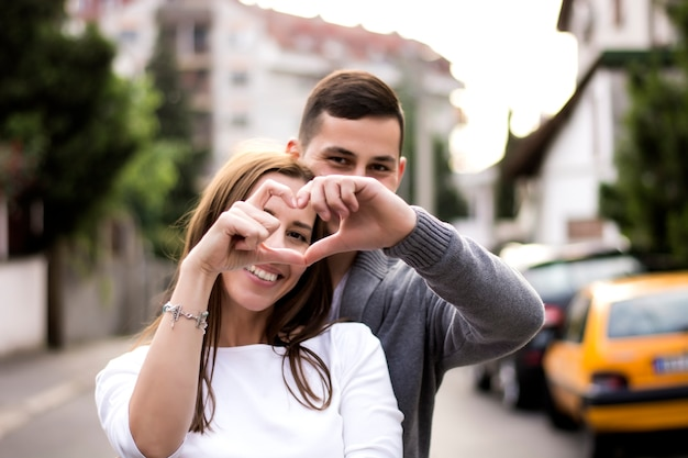 Smiling couple forming a heart shape with their hands at street