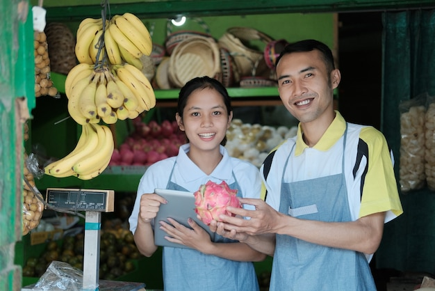 Smiling couple of fruit sellers stood up while holding a dragon fruit and looked at the camera at