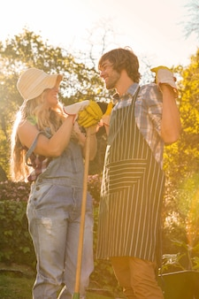 Smiling couple in the garden holding a rake