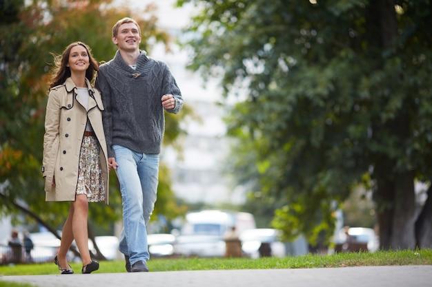 Улыбаясь пара собирается на прогулку на открытом воздухе