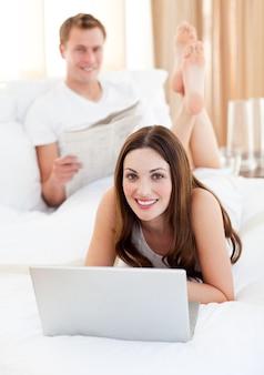 Улыбаясь пара, имеющих активность, лежа на кровати