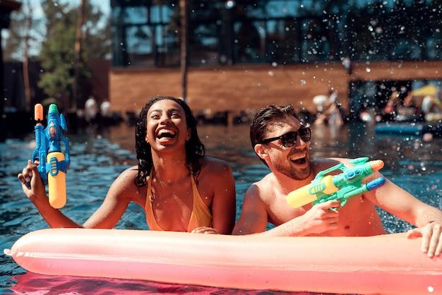 Smiling couple having fun in swimming pool