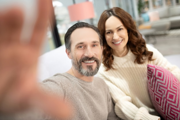 自撮りを作る家具サロンで楽しい時間を過ごしている笑顔のカップル
