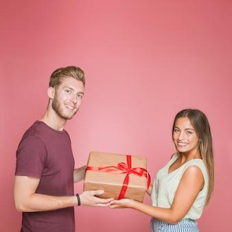 ピンクの背景に赤いサテンのリボンでギフトボックスを保持している笑顔のカップル