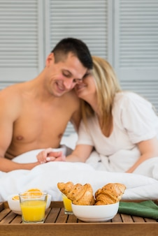 Smiling couple holding hands in bed near food on breakfast table