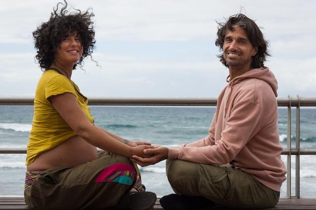 グランカナリア島のビーチのそばのベンチで蓮のポーズに座って手をつないで笑顔のカップル