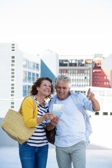 Smiling couple holding map in city