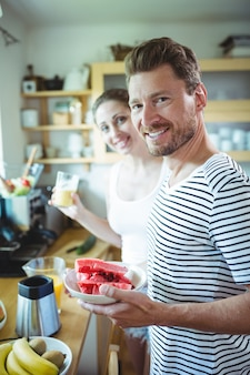 Smiling couple holding plate of water melon in kitchen