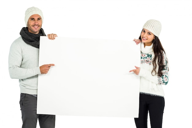 Smiling couple holding and pointing white sheet