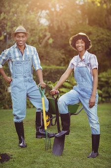 Smiling couple holding shovel and rake in the garden