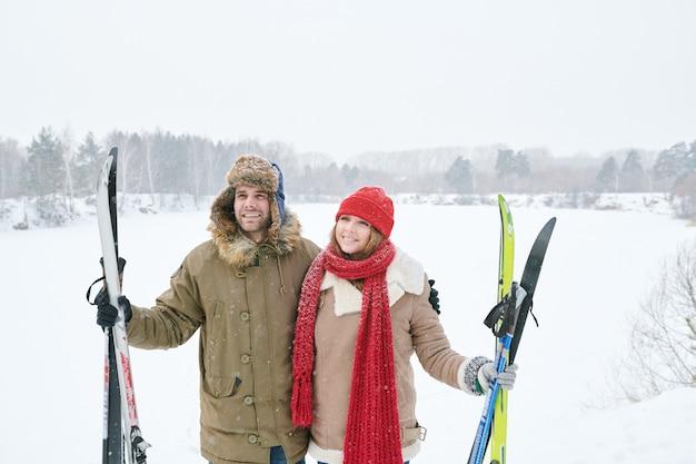 Улыбающиеся пары держат лыжи
