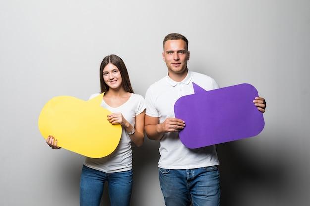 Coppie sorridenti che tengono le nuvole di chiacchierata gialle e blu nelle loro mani isolate su fondo bianco