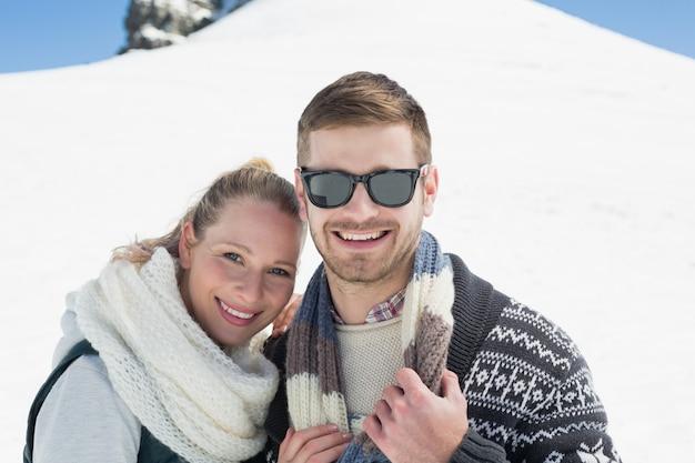 Улыбающаяся пара перед заснеженным холмом