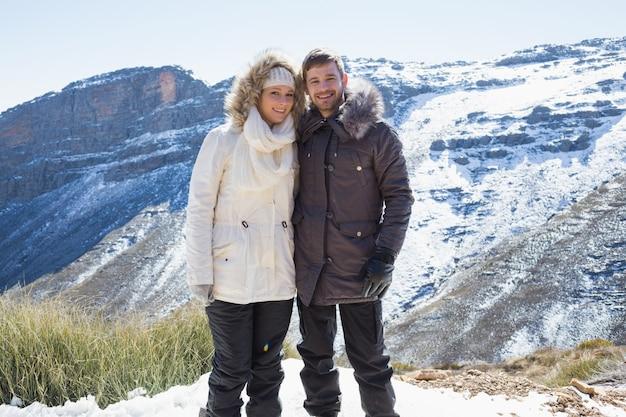 Улыбающаяся пара в меховых куртках с снежным горным хребтом